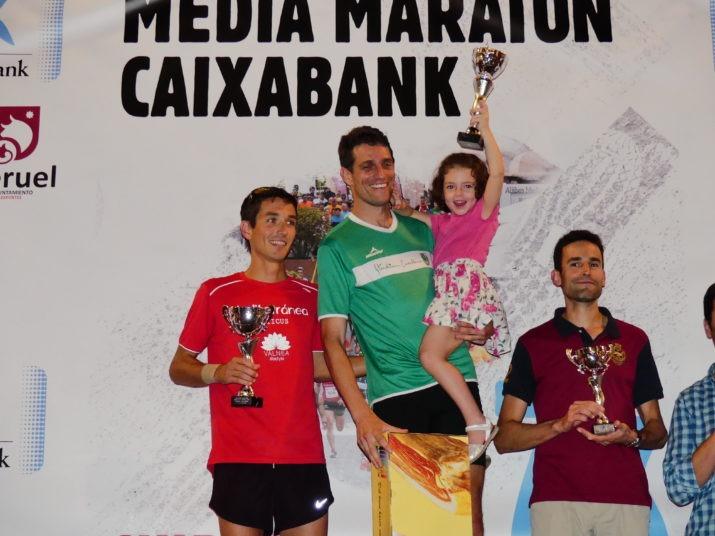Los ganadores senior de la Media Maratón  y una niña feliz